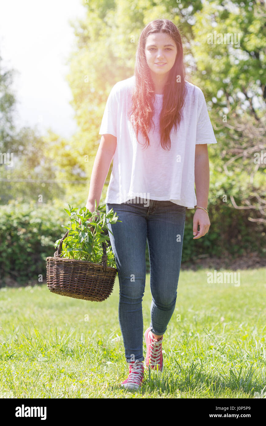 Young woman gardening and smiling - Stock Image
