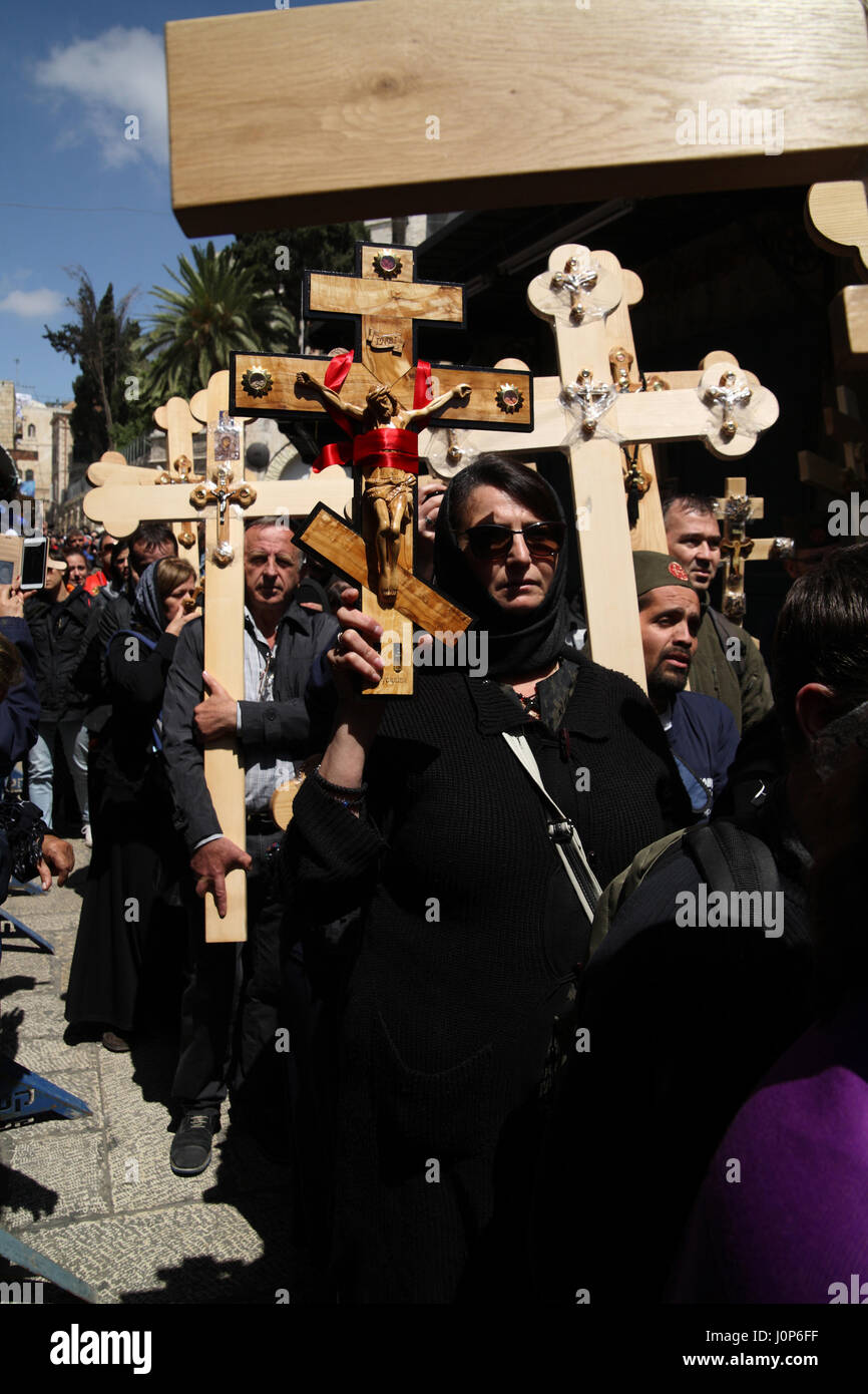 Good Friday Procession on the Via Dolorosa, Serbian pilgrims walk carrying ornamented crosses while uttering the - Stock Image