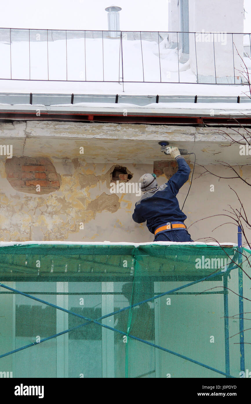 The worker in protective glasses and a respirator processes the wall with an angle grinder before restoration and Stock Photo