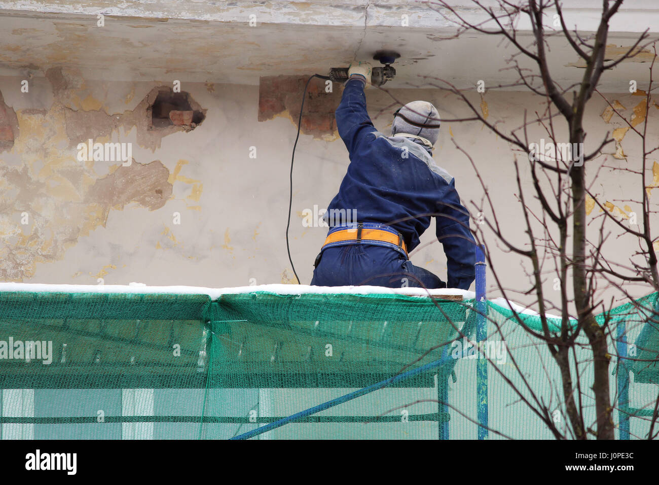 The worker in protective glasses and a respirator processes the wall with an angle grinder before restoration and - Stock Image