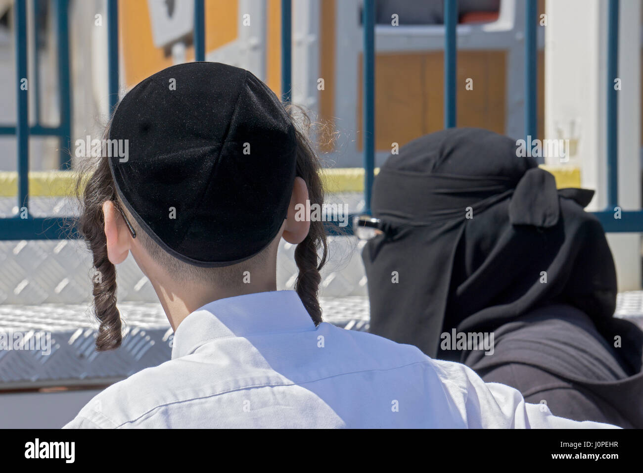 An orthodox religious Jewish boy standing next to a Muslim woman in a hijab at Luna Park in Coney Island, Brooklyn, - Stock Image