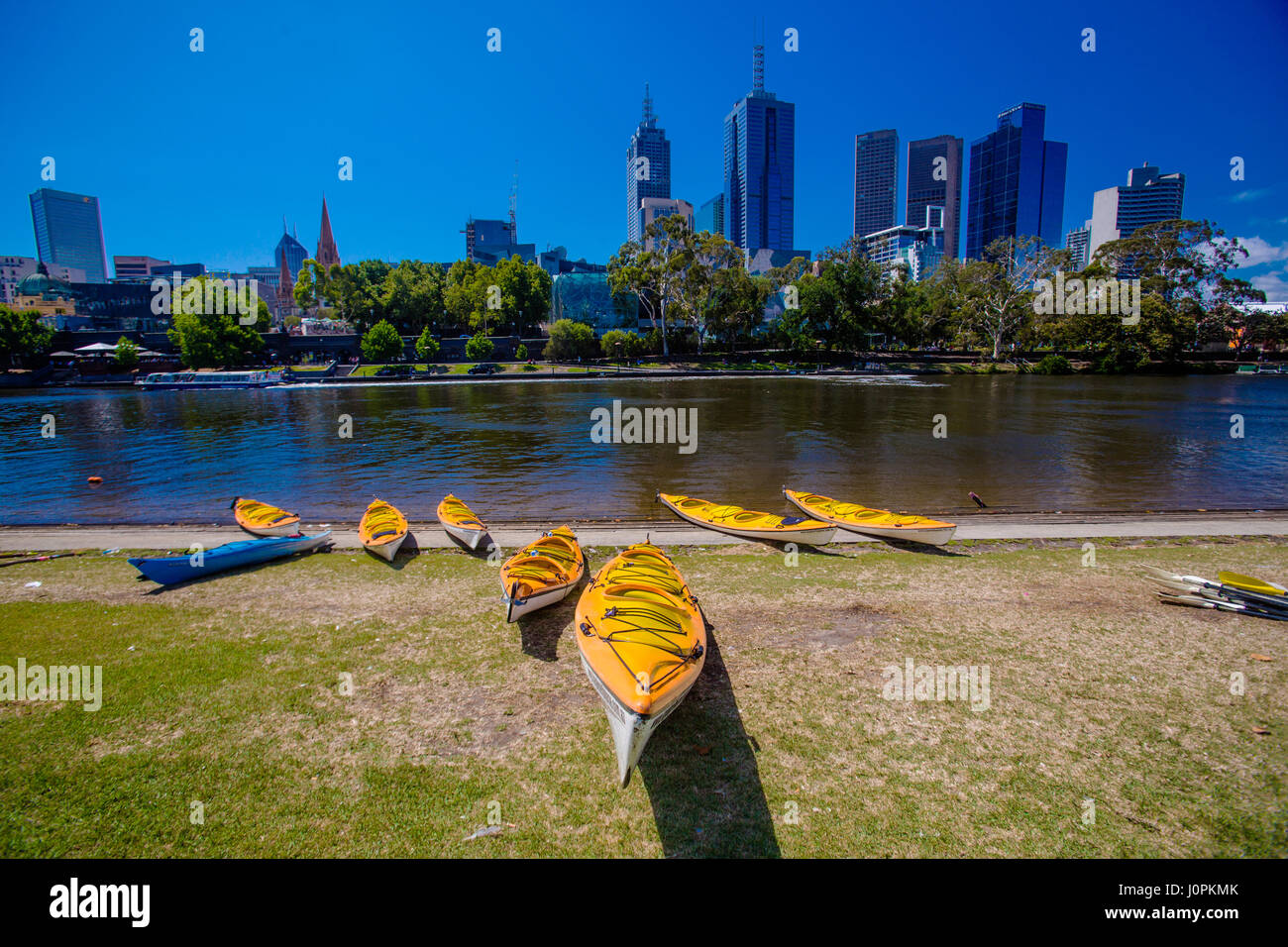 Several kayaks wait for customers next to the Yarra river and the CBD of Melbourne. - Stock Image
