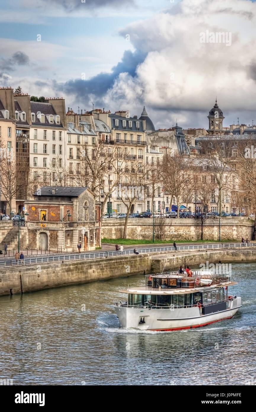 Tourist ship floats on the Seine river and quai des Célestins. Paris. France - Stock Image