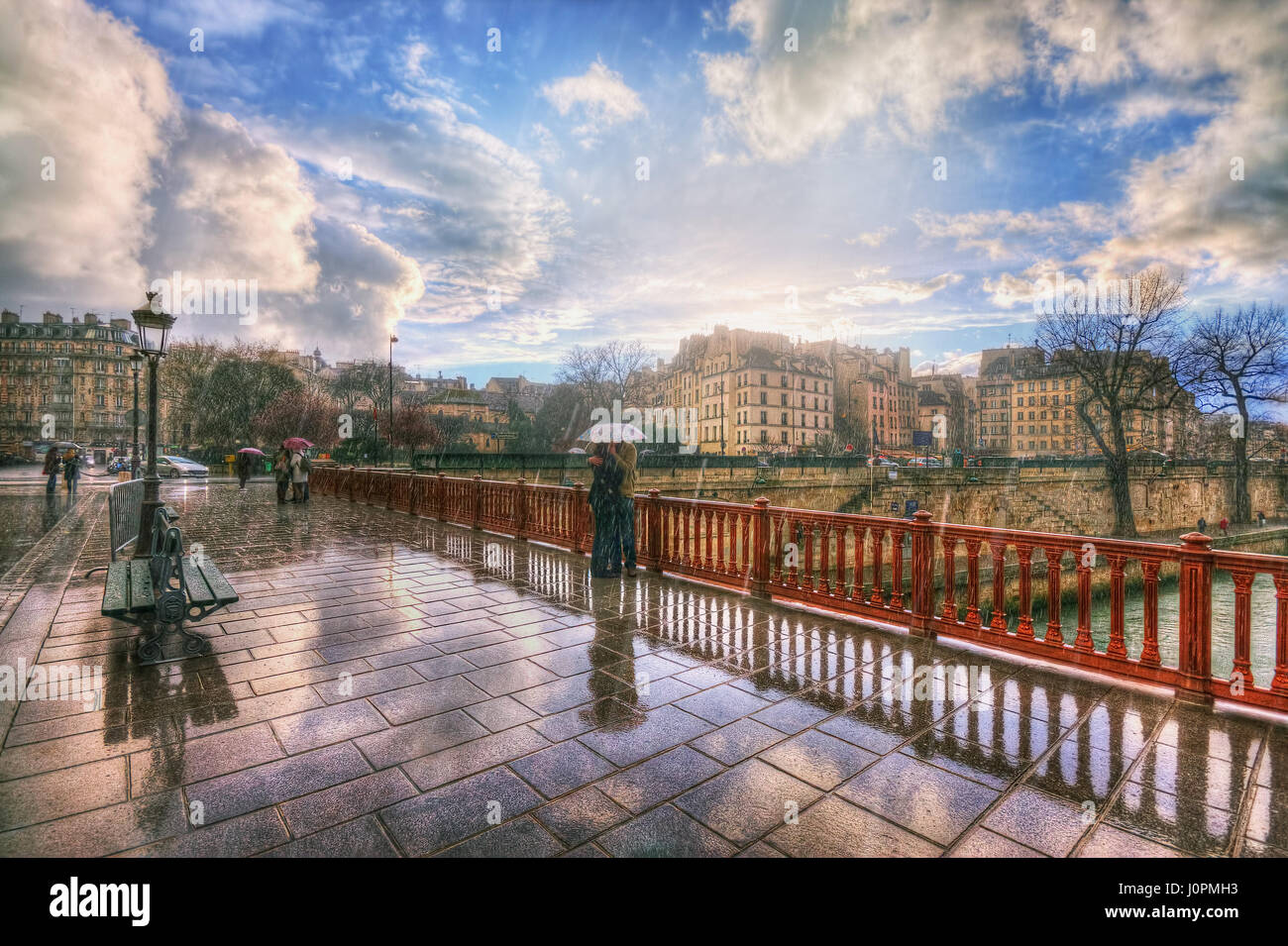 Lovers in the rain on the Pont au Double. France. Paris - Stock Image