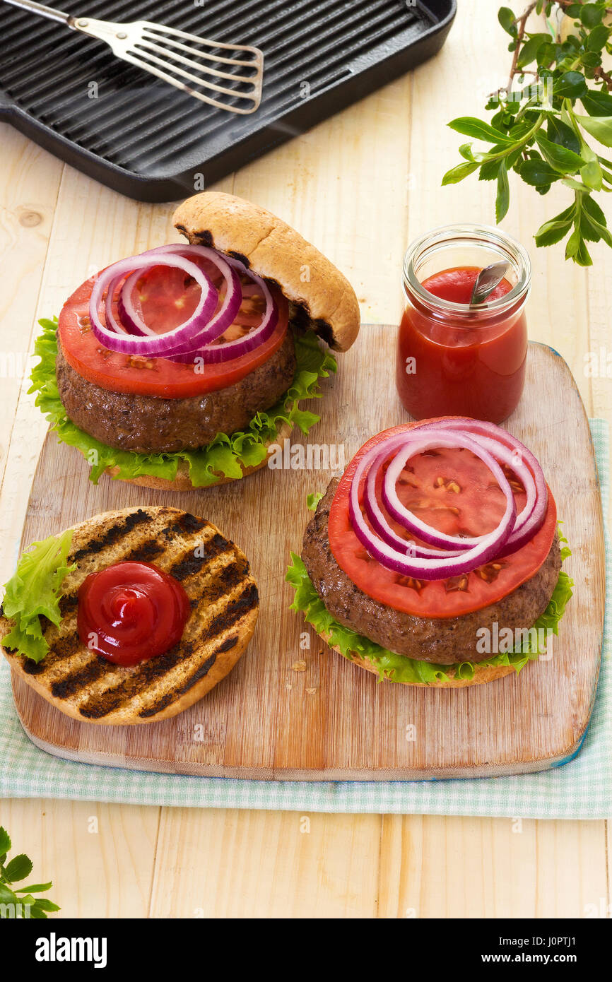 Burger with lettuce tomato red onion on grilled buns with ketchup - Stock Image