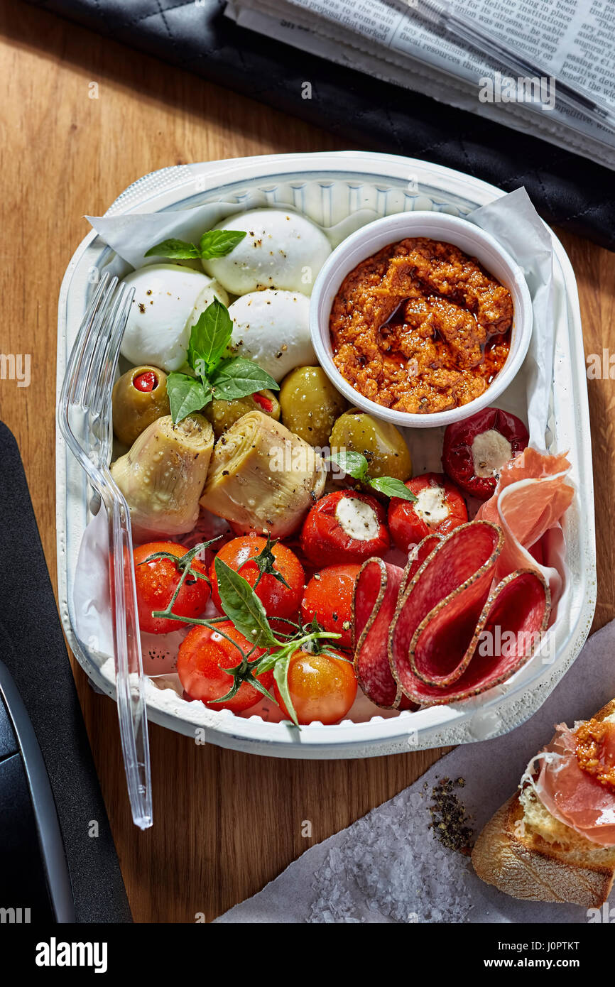 Antipasti lunch office - mozarella, artichoke, salami, red pesto, cherry tomatoes and feta stuffed peppers - Stock Image