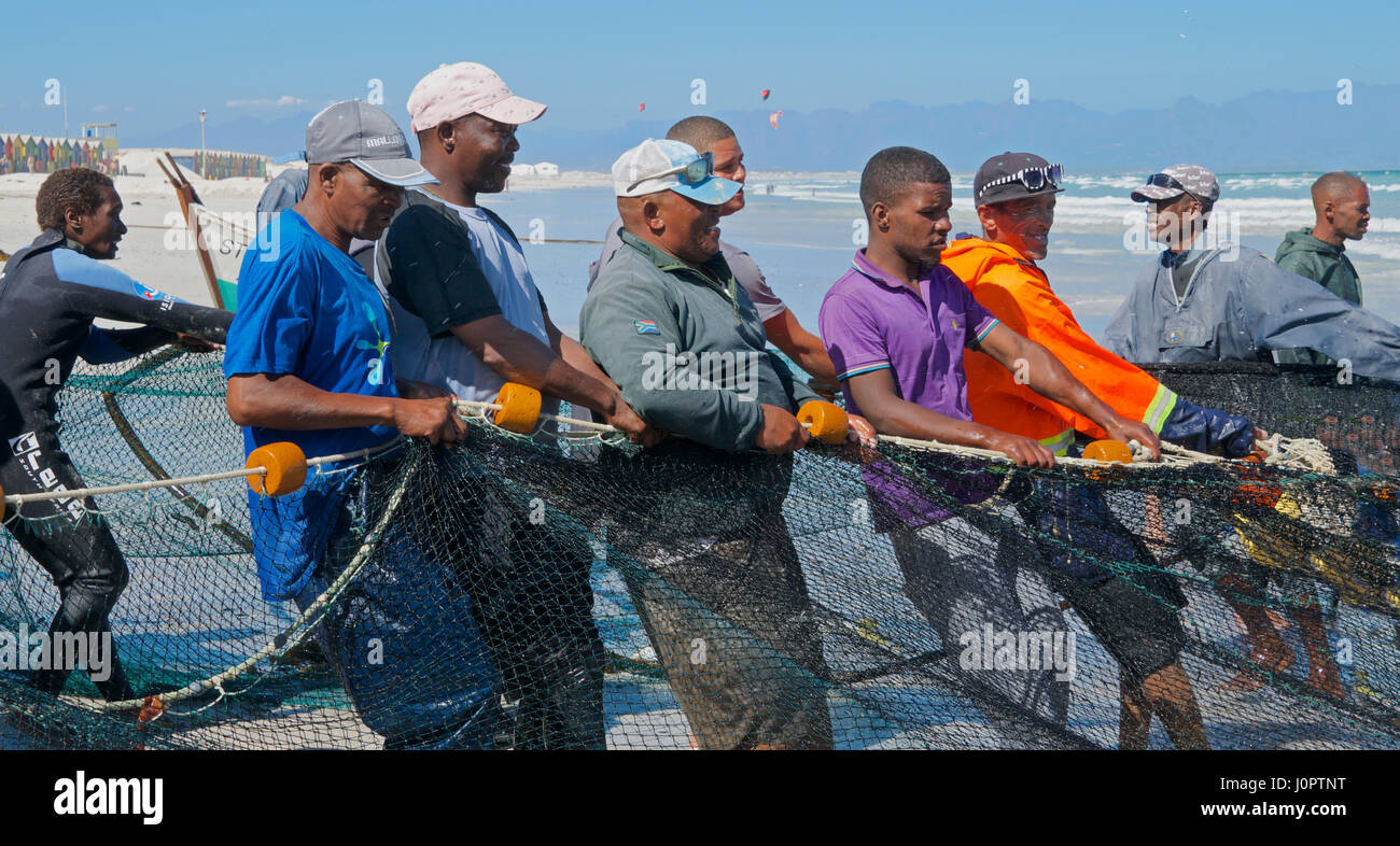Fishermen hauling and bringing in the catch Muizenberg Beach  Cape Peninsular Cape Town South Africa - Stock Image