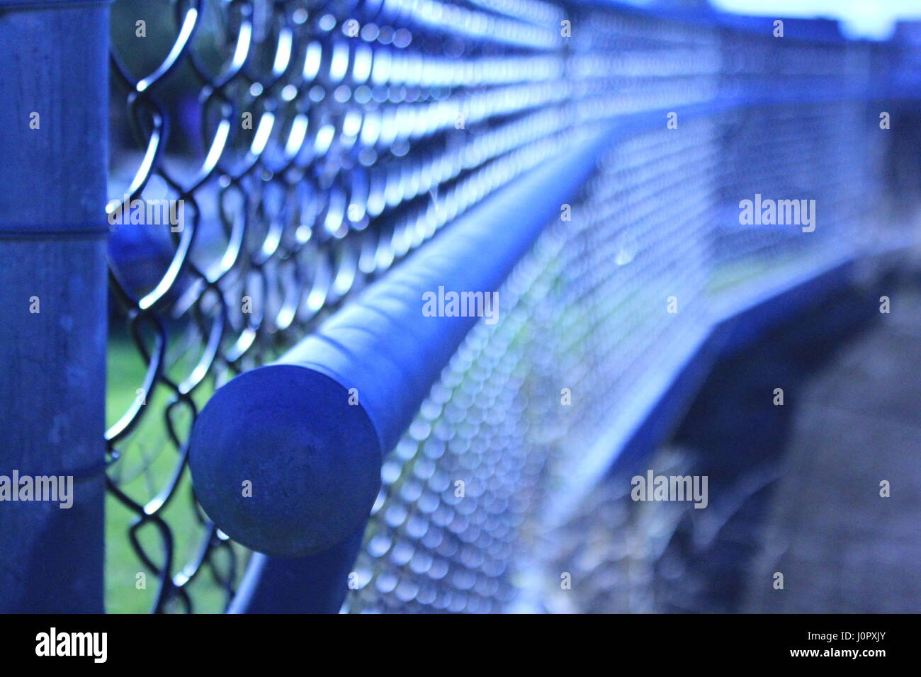 Macro photo of hand rail with soft focus diamond wire fence - Stock Image