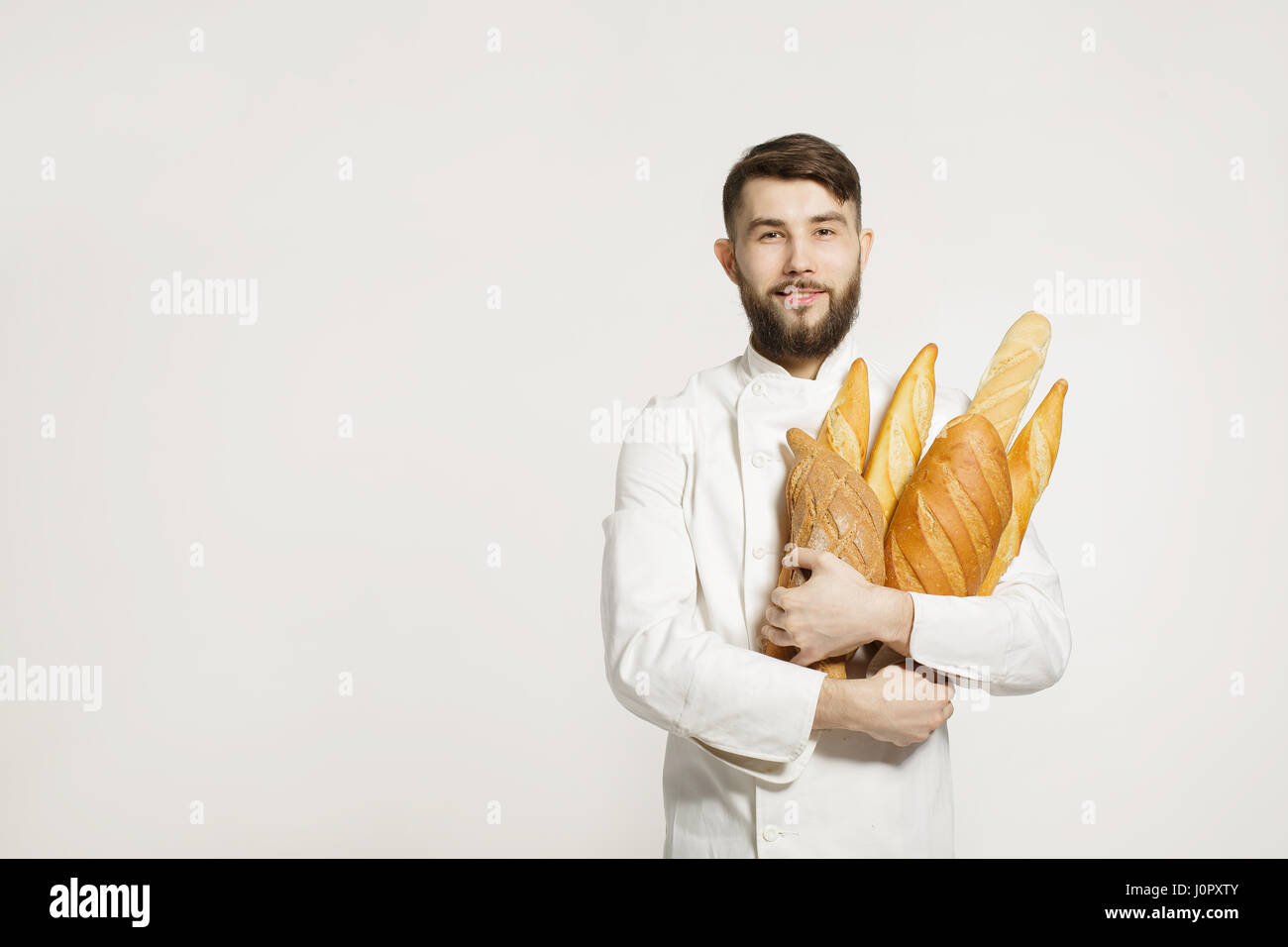 Handsome baker in uniform holding baguettes with bread shelves on the white background. Handsome man holding warm - Stock Image
