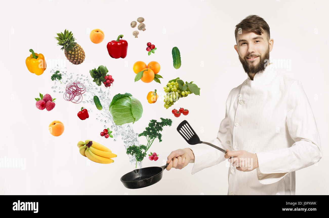 Handsome professional chef in uniform uggling with vegetables and ...