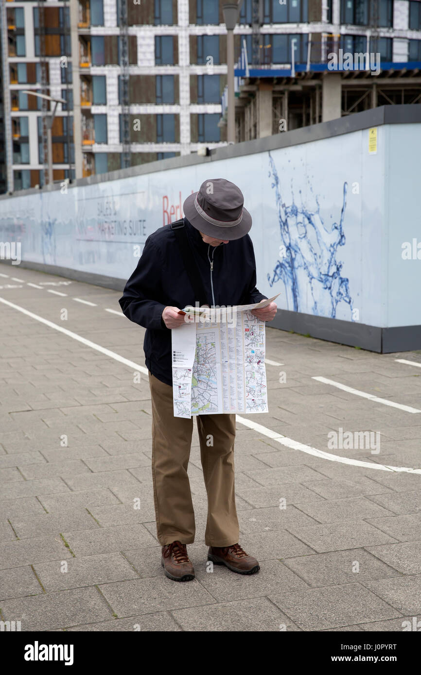 A man looks at a map in Woolwich Arsenal London - Stock Image