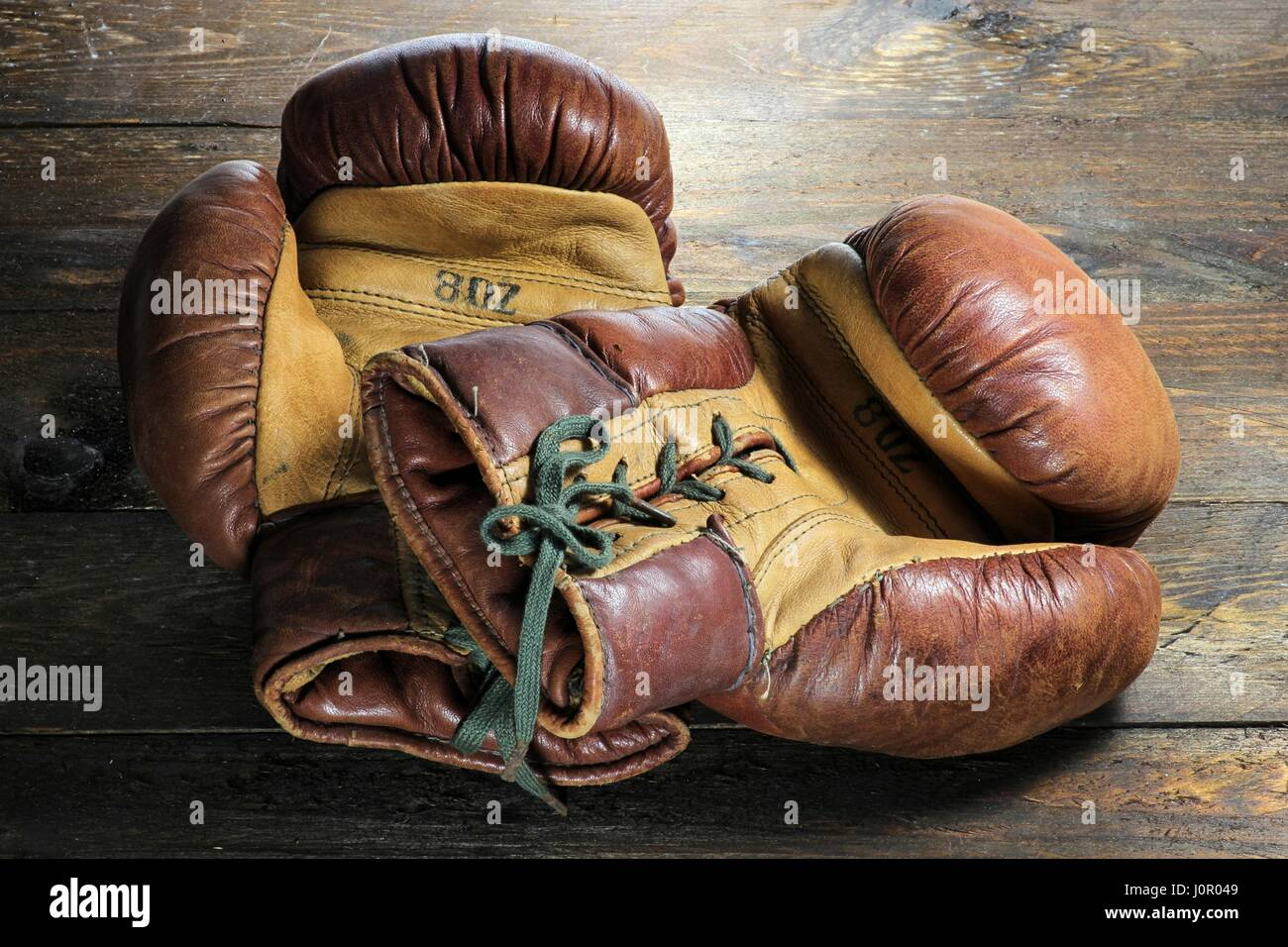 vintage boxing gloves on wooden background - Stock Image