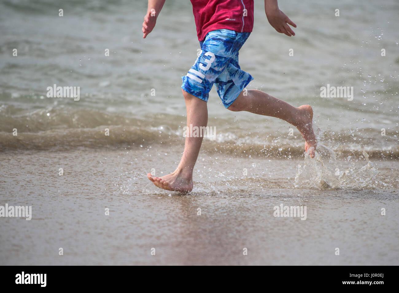 Fistral Newquay Person running along shoreline Splash Splashing Runner Spray Water Barefoot Energy Energetic Seaside - Stock Image