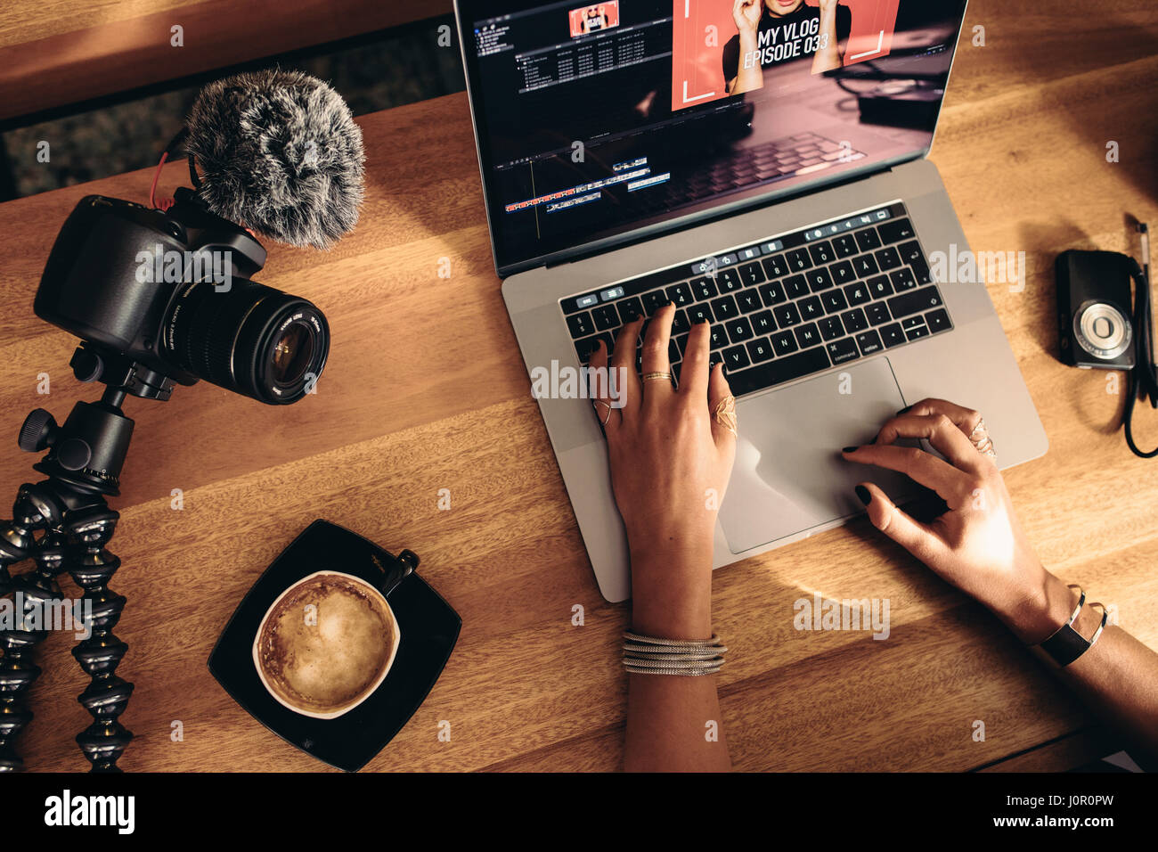Top view of female vlogger editing video on laptop. Young woman working on computer with coffee and cameras on table. - Stock Image