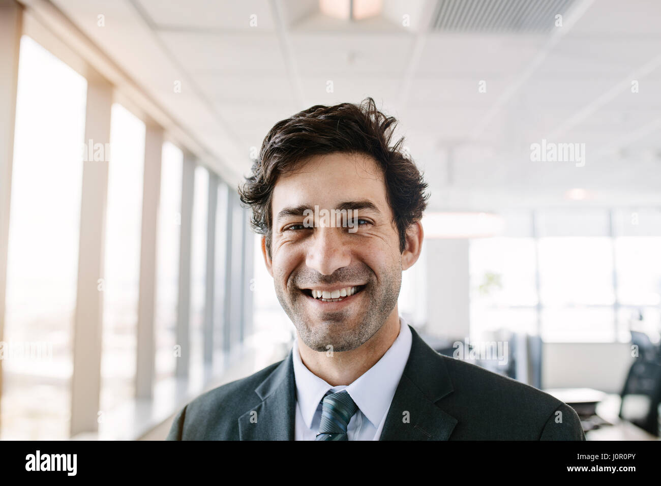 Portrait of successful young businessman standing in office. Manager in suit looking at camera with a smile. Stock Photo