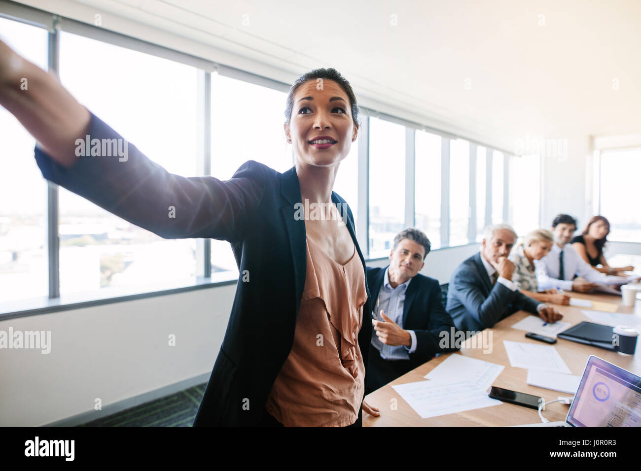 Presentation in modern conference room with asian businesswoman showing something important to colleagues sitting - Stock Image