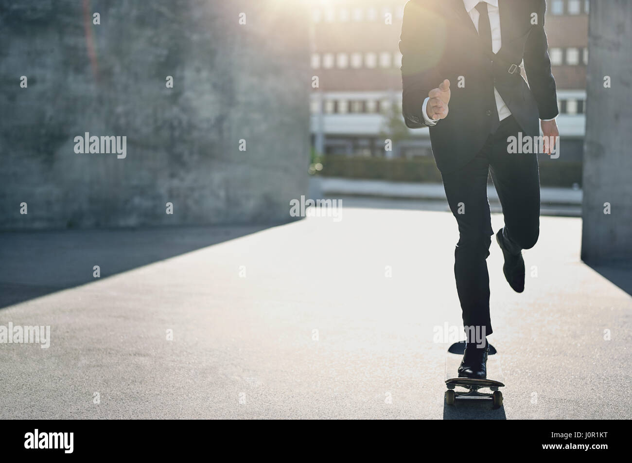 Horizontal crop shot of a businessman wearing formal suit riding a skateboard in the city. - Stock Image