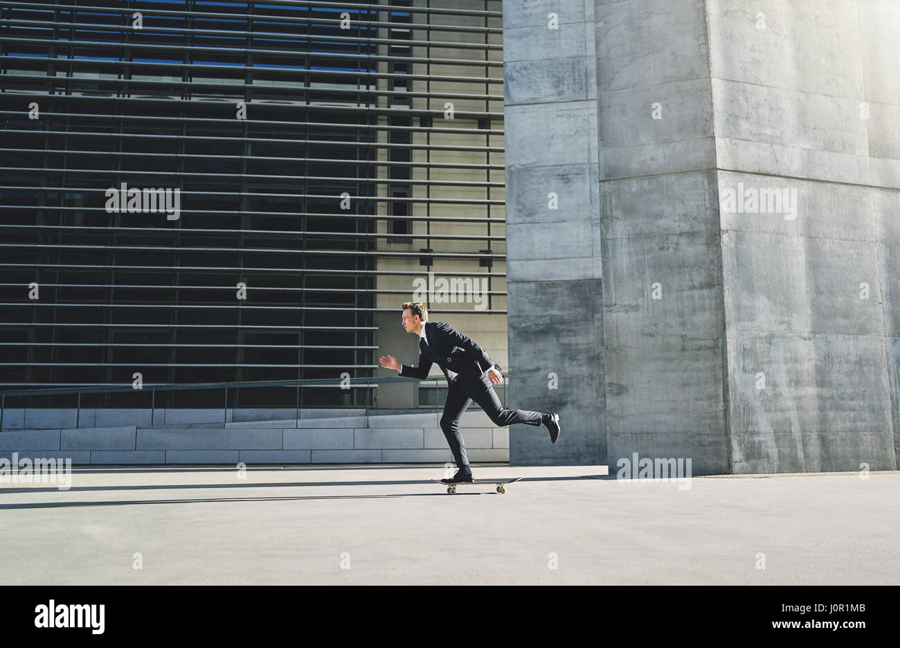 Businessman in a suit moving with high speed on a skateboard - Stock Image