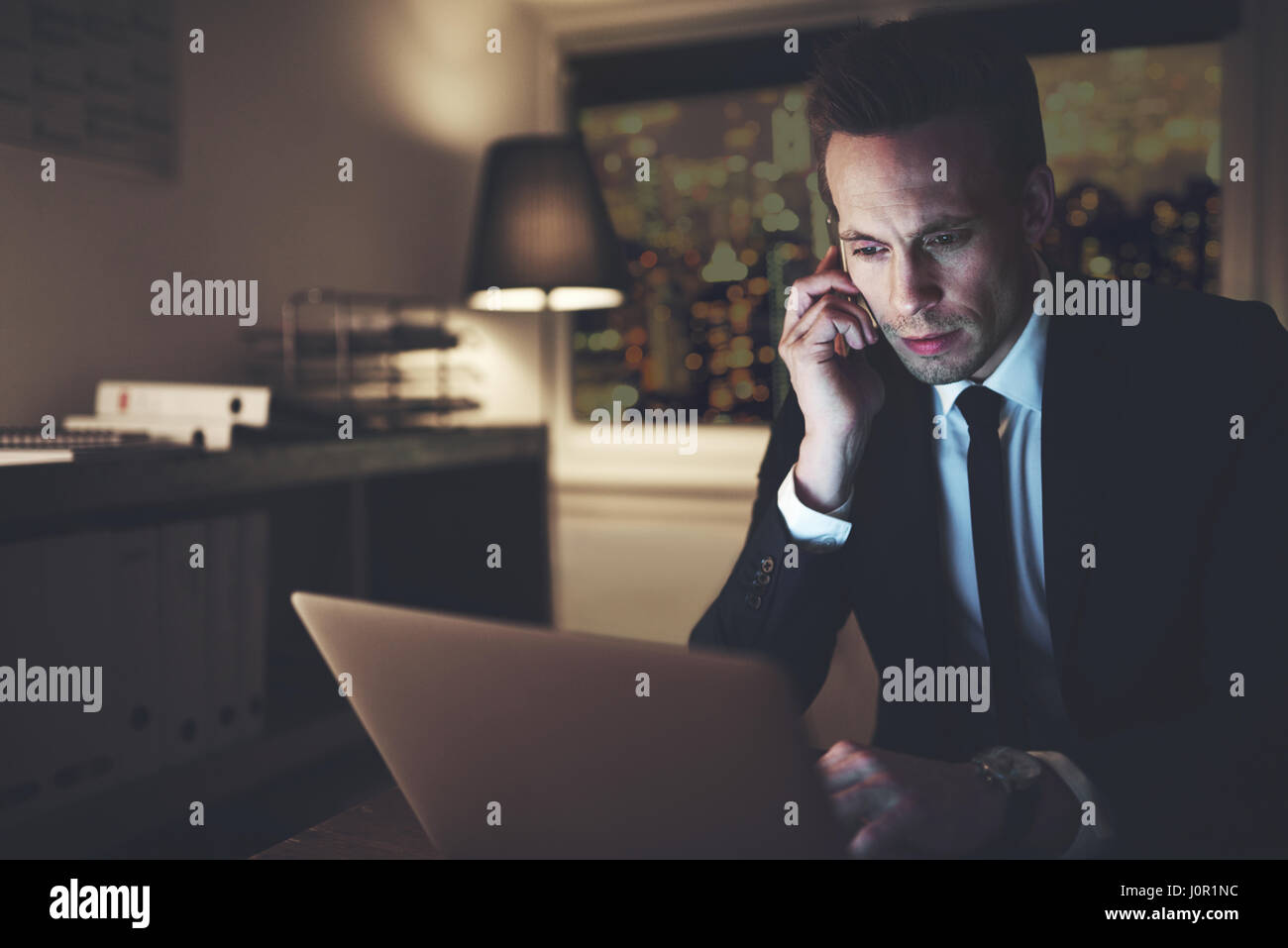 Thoughtful businessman in the office browsing laptop and talking smartphone while taking overtime. - Stock Image