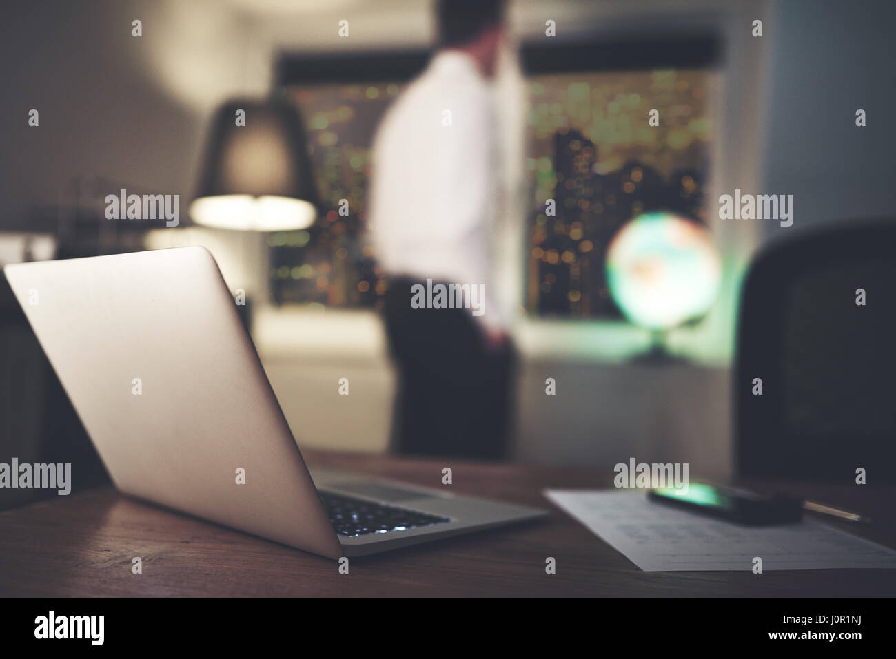 An unrecognizable blurred accountant standing in the office and thinking at night. Stock Photo