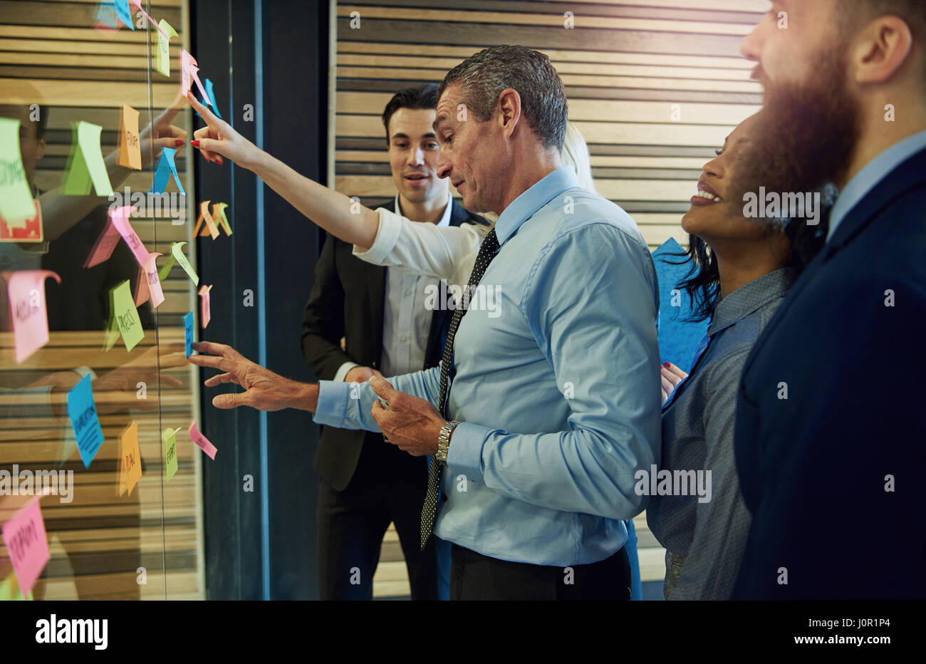 Business people standing at the wall with the stickers and communicating during the meeting. - Stock Image