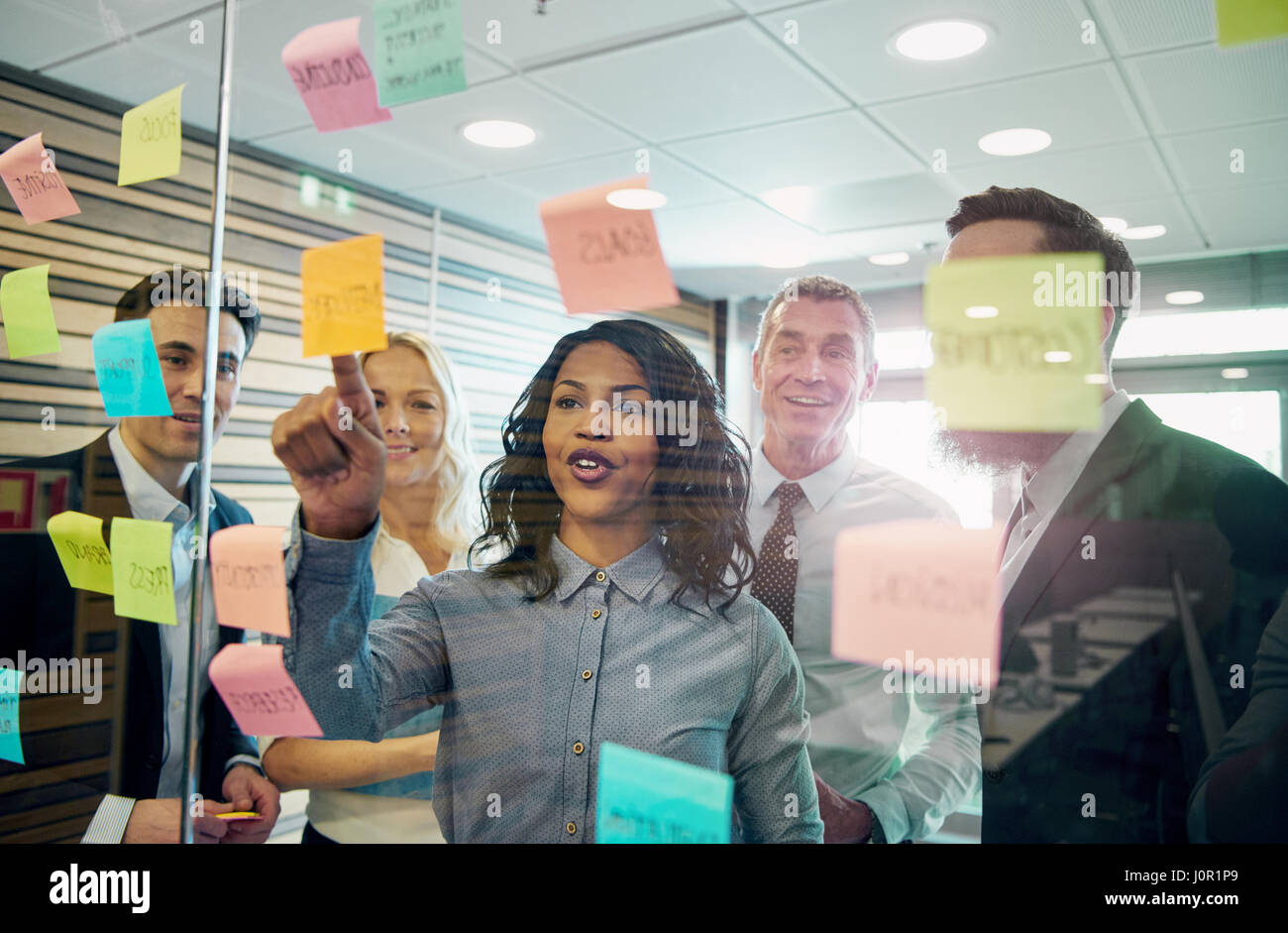 Business people in office cooperating at the wall with the stickers. Mixed team of entrepreneurs - Stock Image