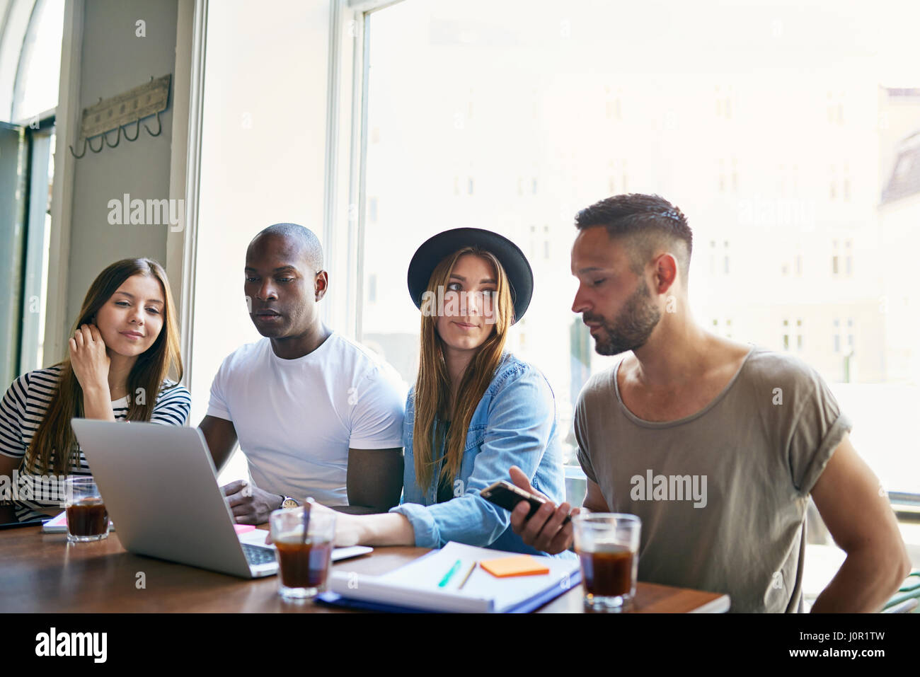 Group of four young co-workers sitting at table with laptop and having coffee while discussion in office. - Stock Image