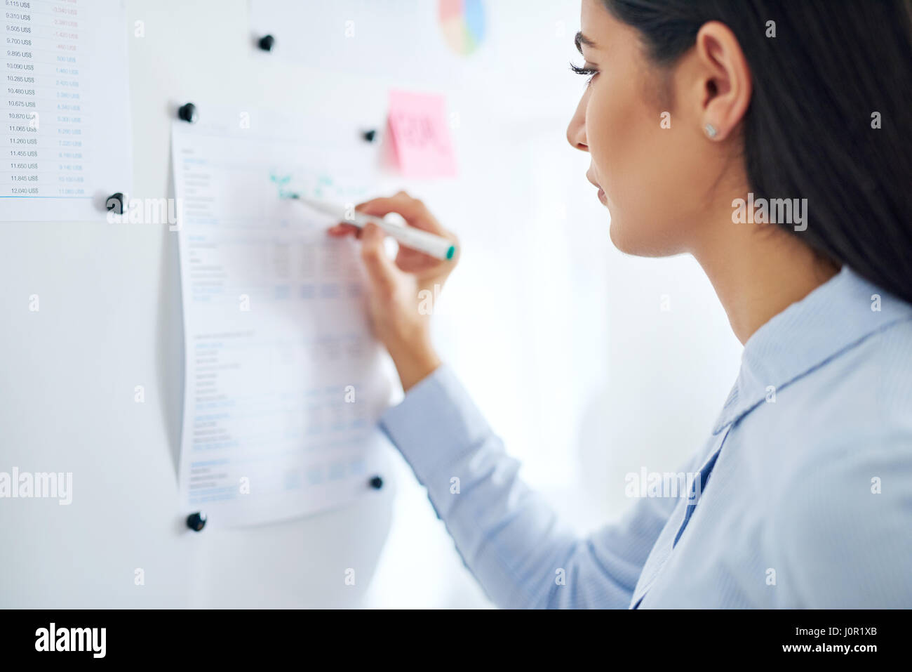 Close up rear three quarter view on single woman writing information on chart in office setting - Stock Image