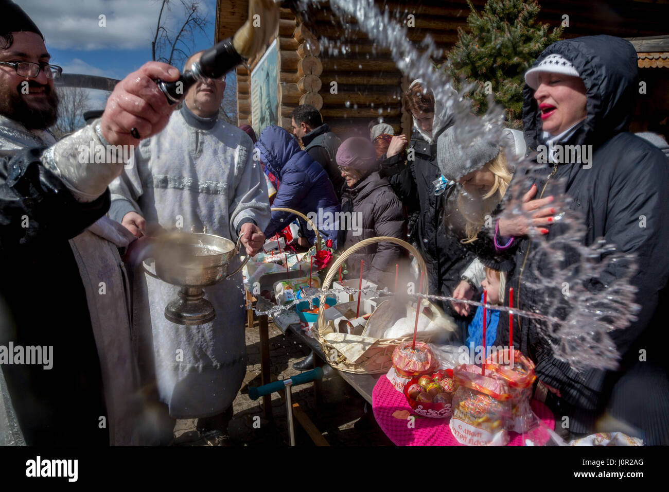 Russian people celebrate Easter on the streets of Moscow. An Orthodox priest conducts the ceremony of consecration - Stock Image