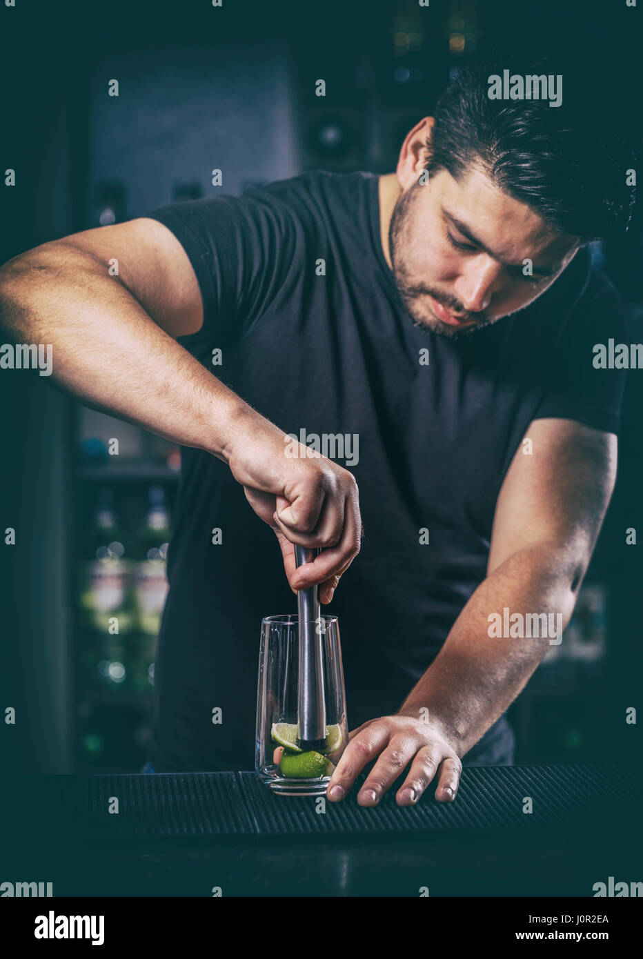 Bartender crushed with a muddler lime for mojito cocktail - Stock Image