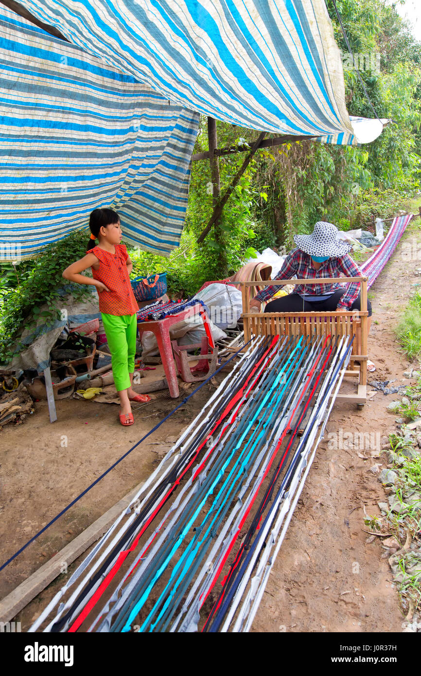 Woman working at loom, weaving extended rug  (18 meters) to be section into smaller lengths, young daughter observing, - Stock Image