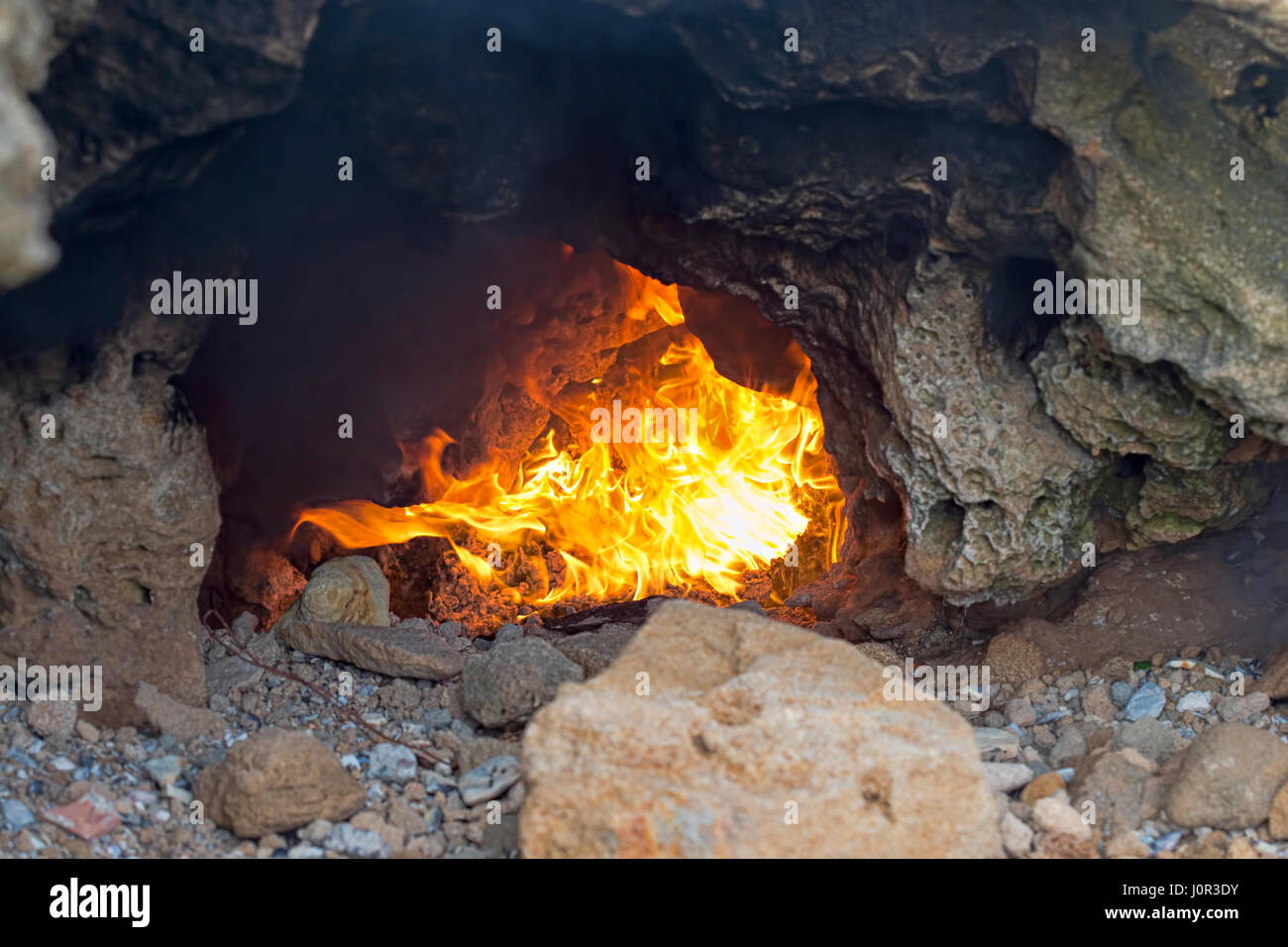 Fire in cave, by the shore, Moroccan village Stock Photo