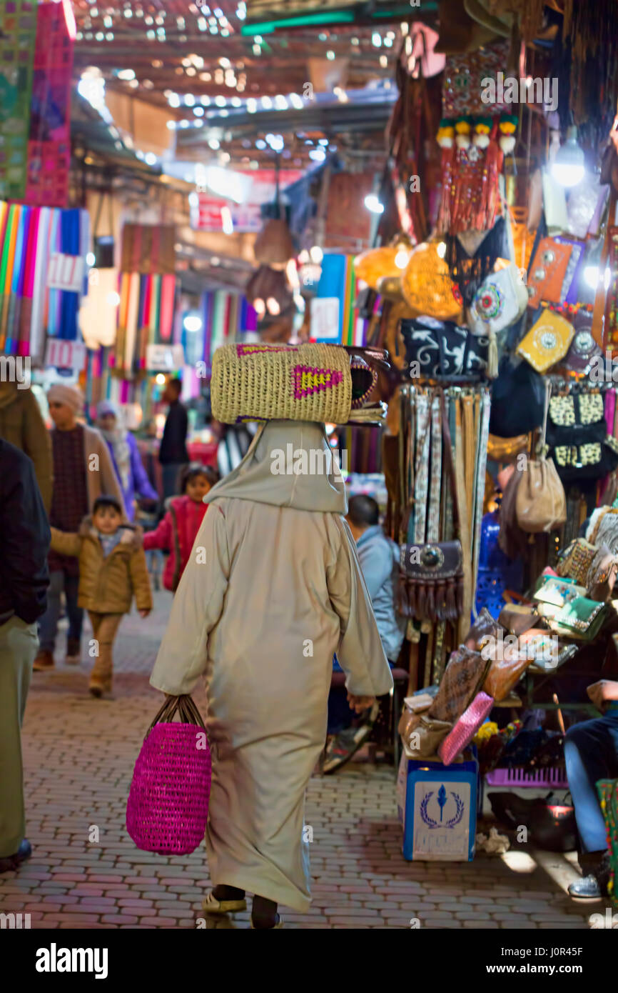Back of a man carrying bag on his head in Marrakesh market city centre area, Morocco Stock Photo