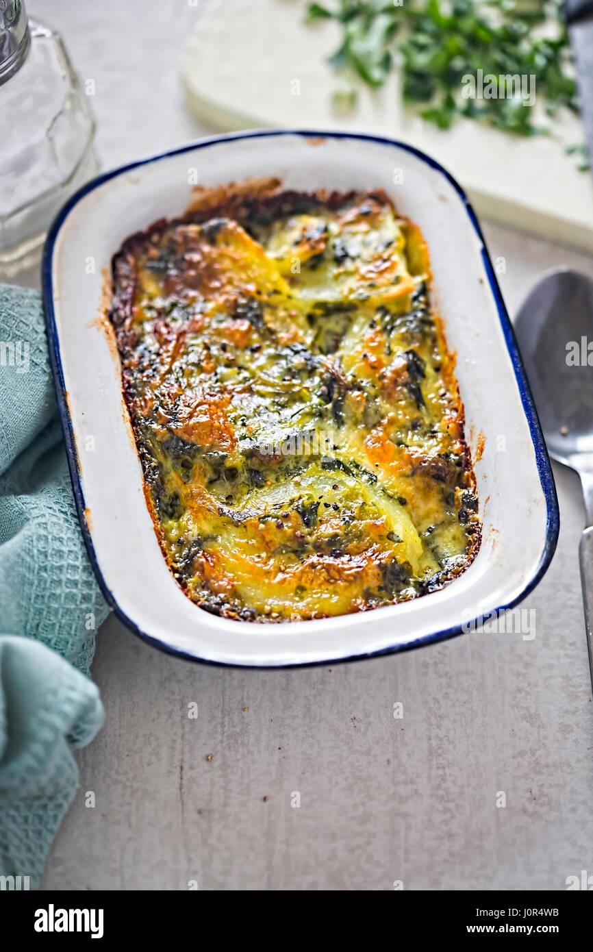 Potato and spinach gratin in creamy garlic sauce - Stock Image
