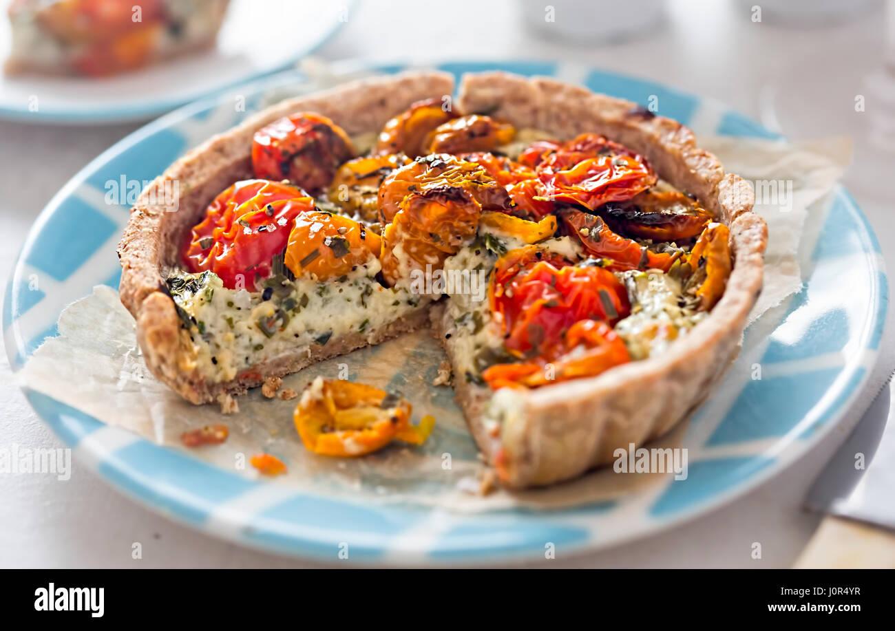 Tomato tart with mozzarella and basil on blue plate - Stock Image