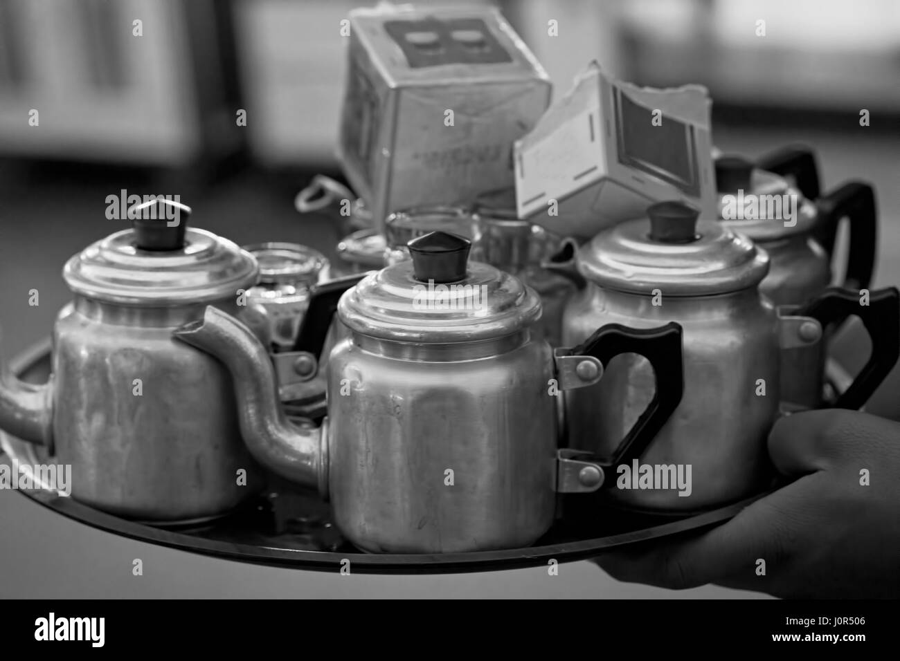 Tray with kettles and tea carried by Moroccan boy - Stock Image