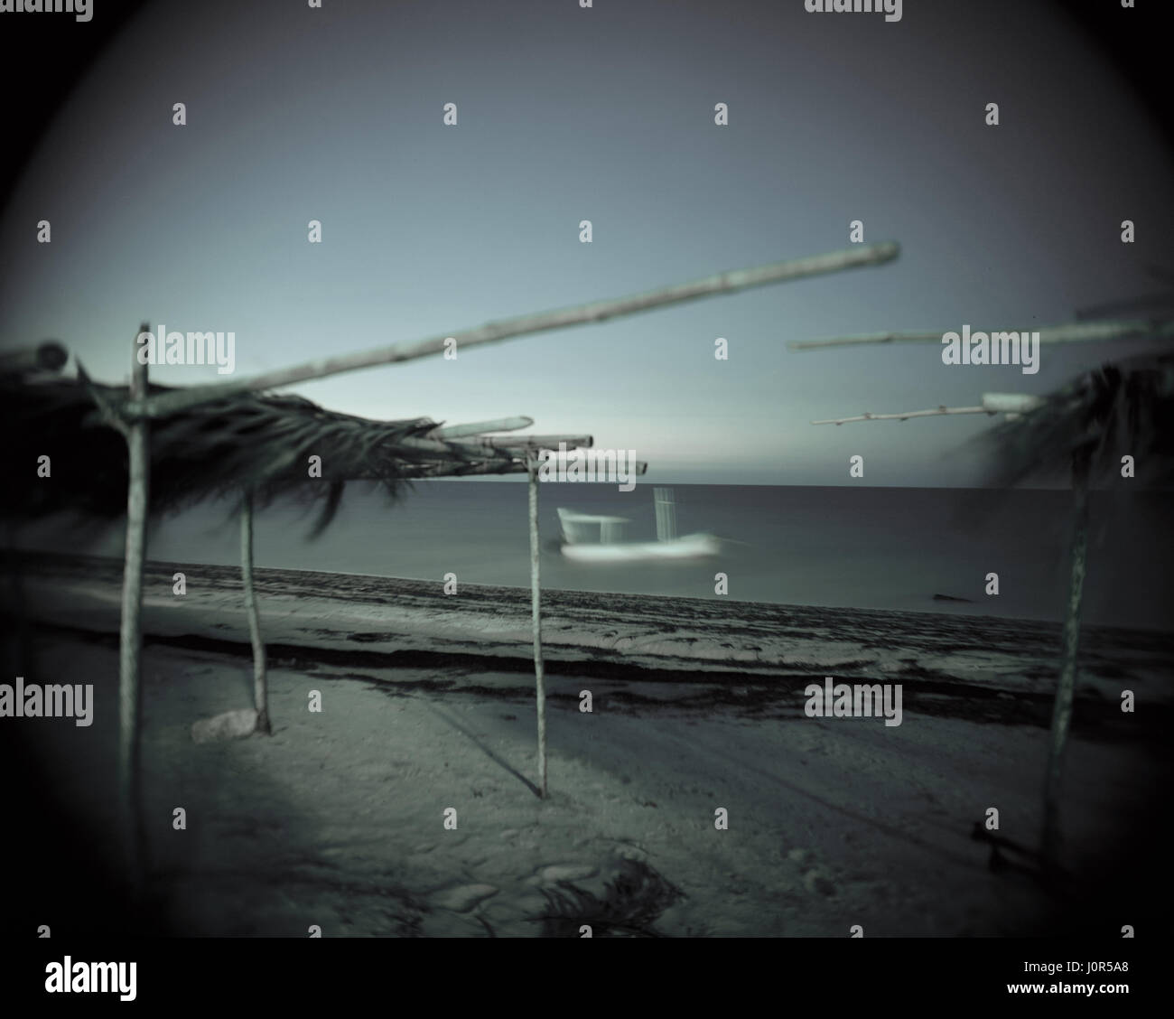 fishing boat on calm sea at night - Stock Image