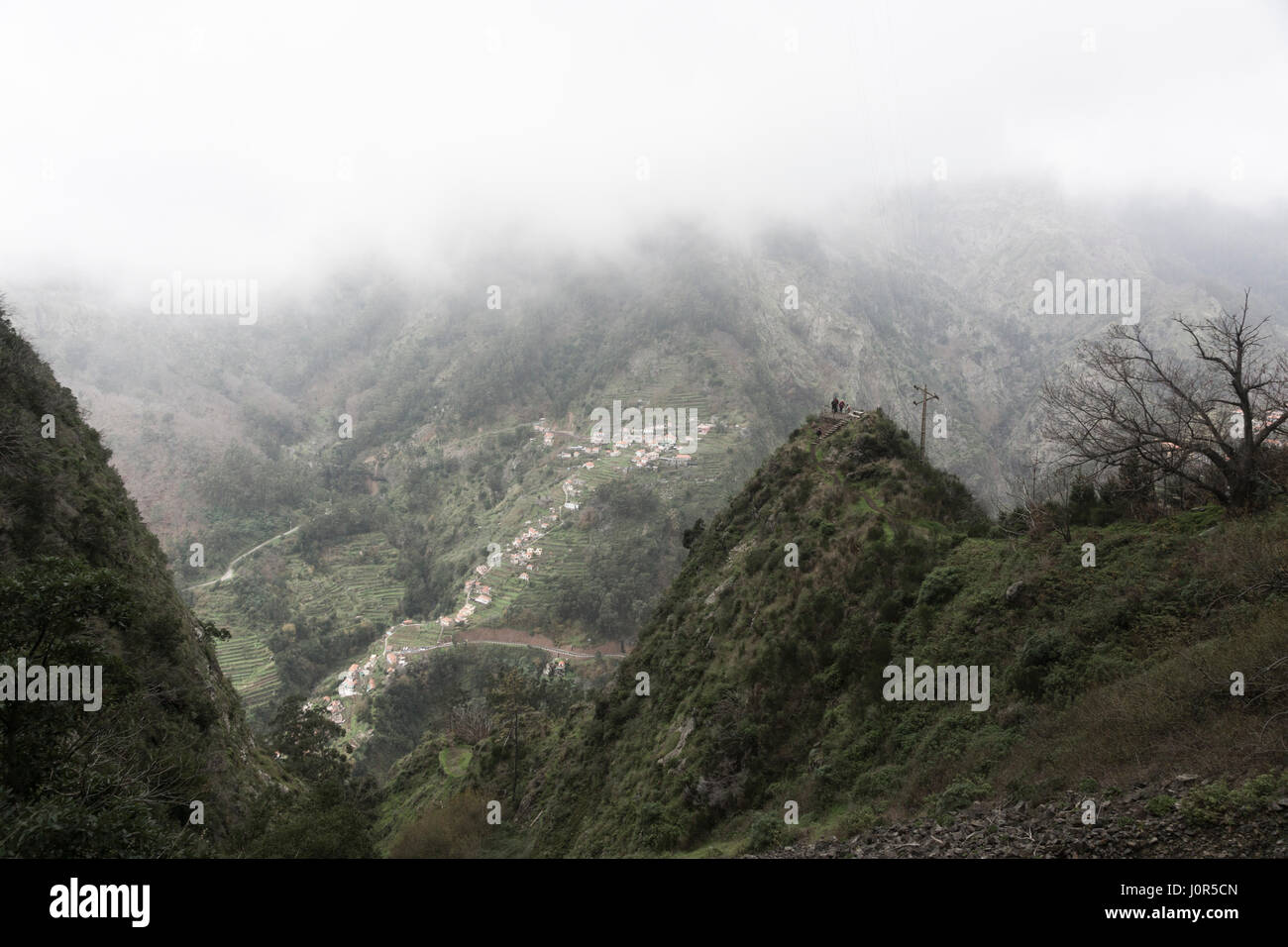 A group of tourists looking out from a promontory down into Curral das Freiras, Madeira - Stock Image