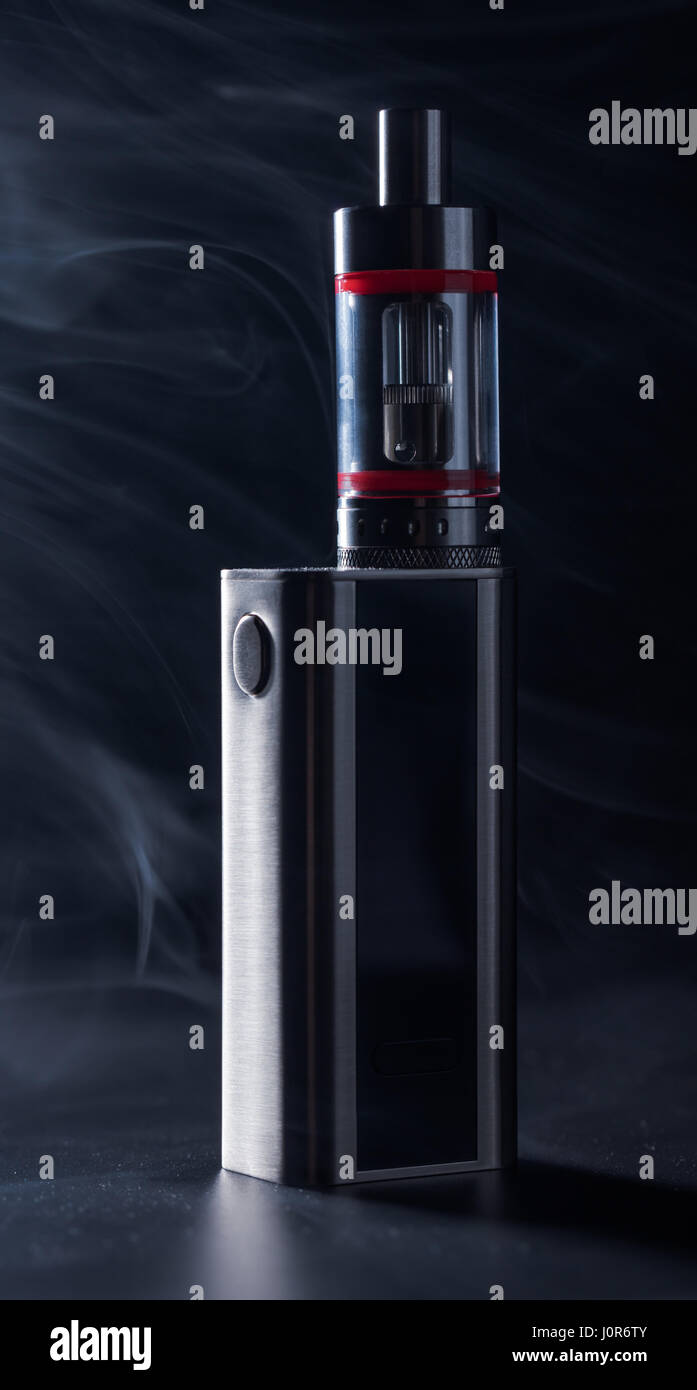 Electronic cigarette on a black background in smoke - Stock Image