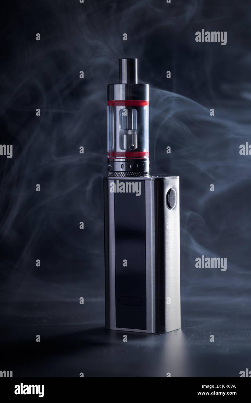Electronic cigarette close-up on a black background in smoke - Stock Image