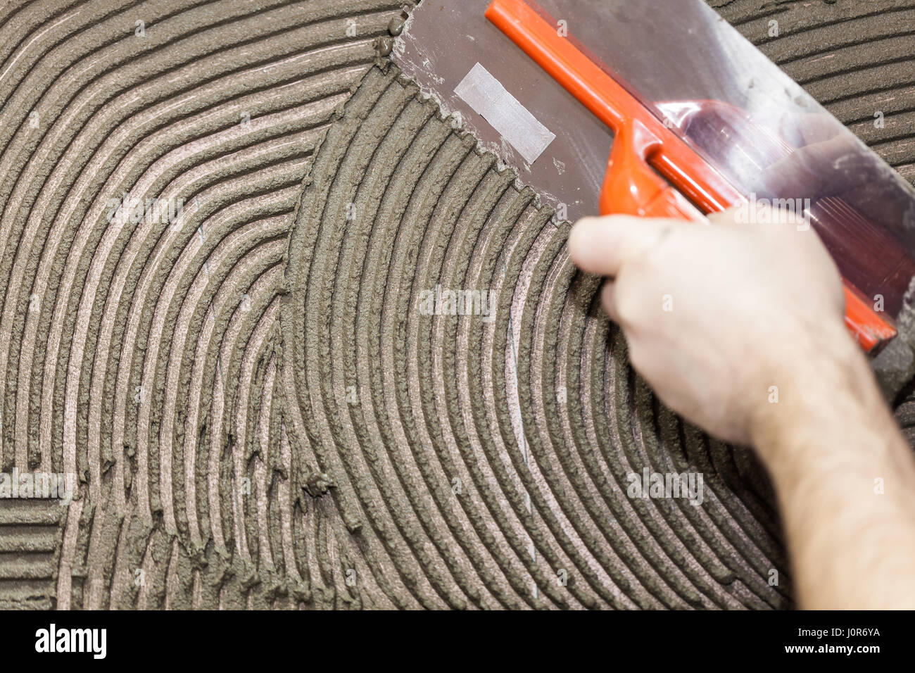 repair work laying tile, trowel in a man hand Stock Photo