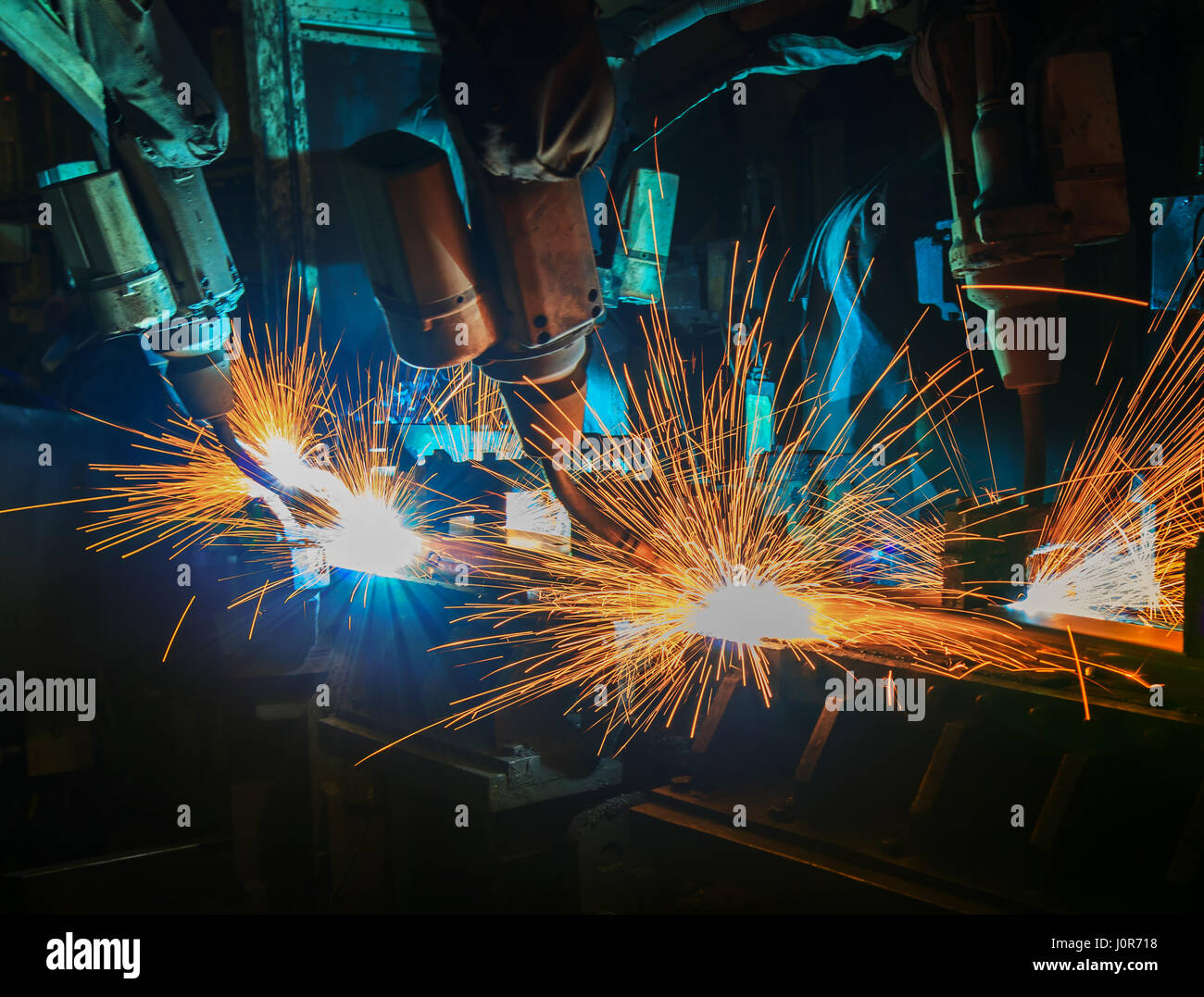 Industrial welding robots in production line manufacturer factory - Stock Image