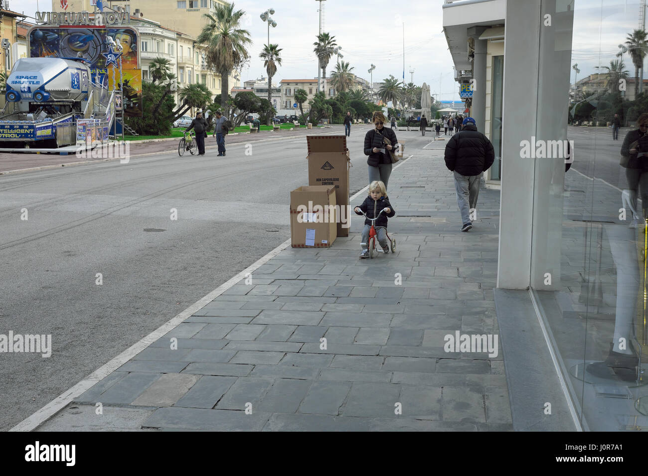 Mother and son - Child cycling on a tricycle and looking at the camera on Viareggio promenade, Tuscany, Italy, Europe - Stock Image