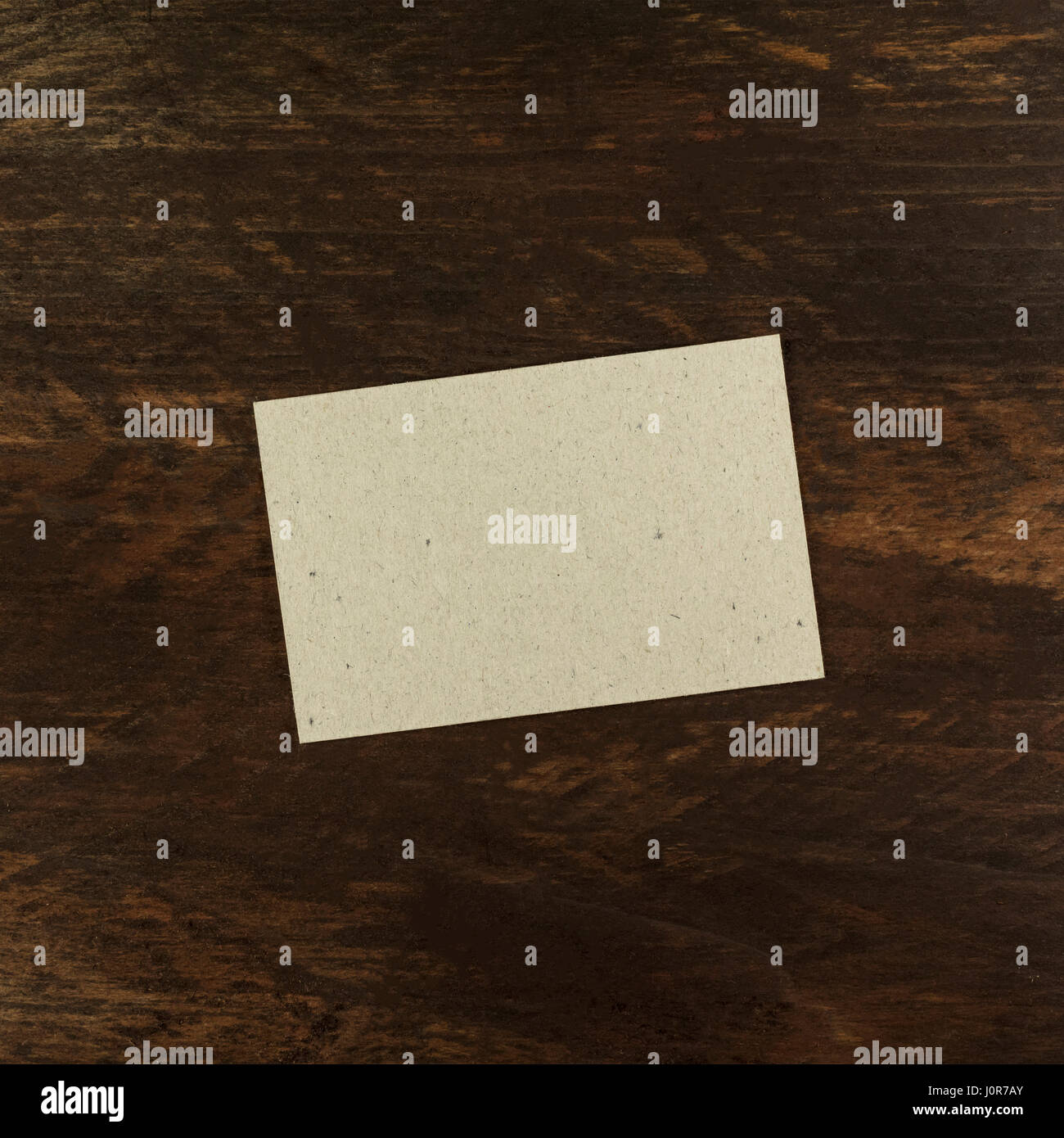 A photo of a grey kraft paper business card on a dark wooden stock a photo of a grey kraft paper business card on a dark wooden background texture a square mockup or a minimalist banner with copyspace reheart Image collections
