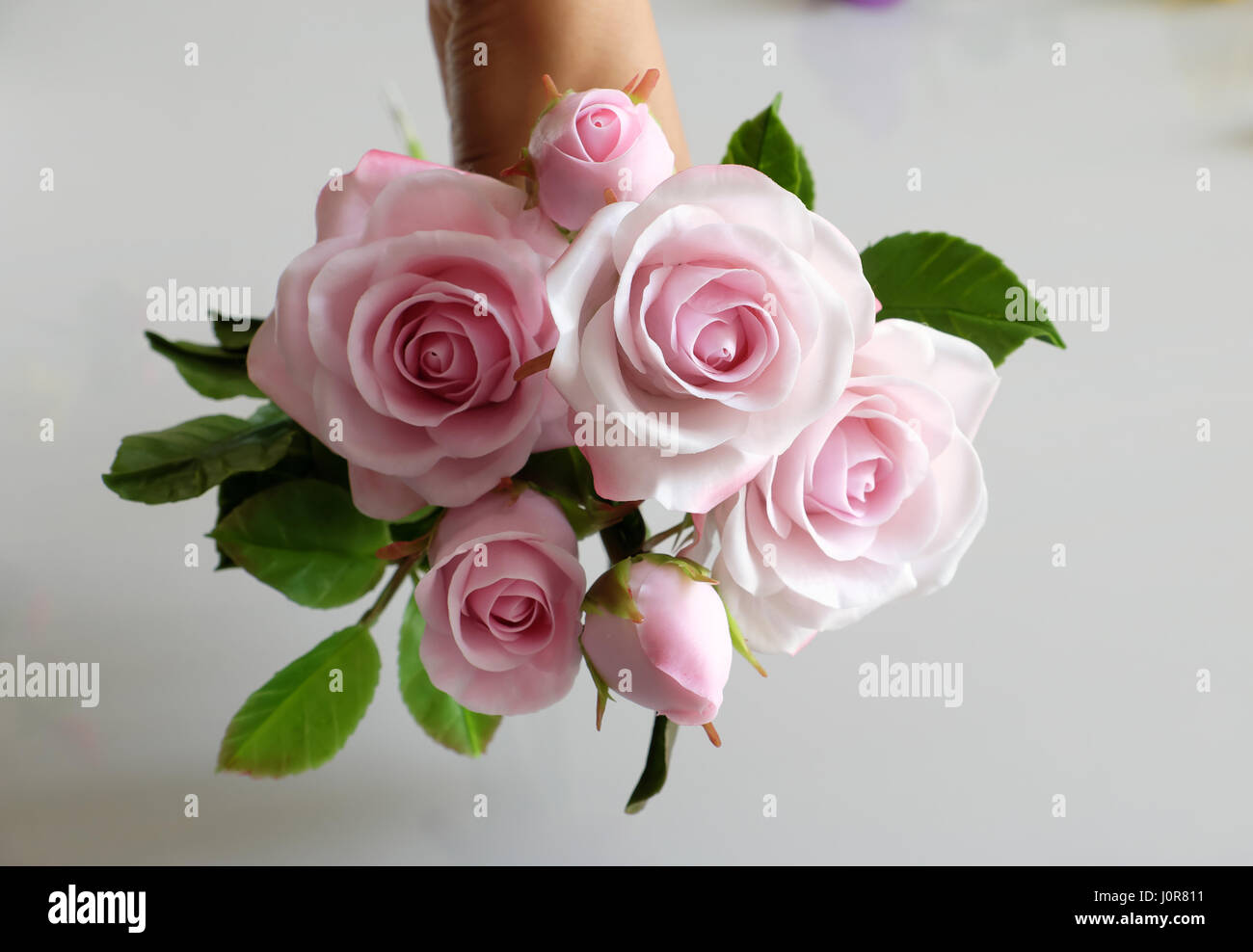 Wonderful clay art woman hand hold bouquet of roses flower in pink wonderful clay art woman hand hold bouquet of roses flower in pink on white background beautiful artificial flowers of craftsmanship with skillful izmirmasajfo