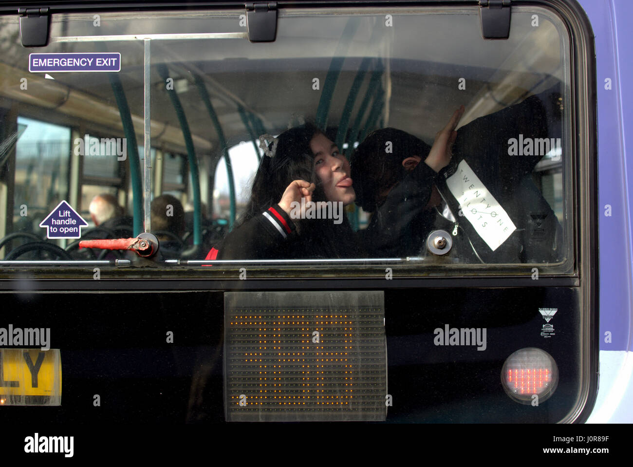 kids messing about pulling faces at back of a bus dabbing Stock Photo