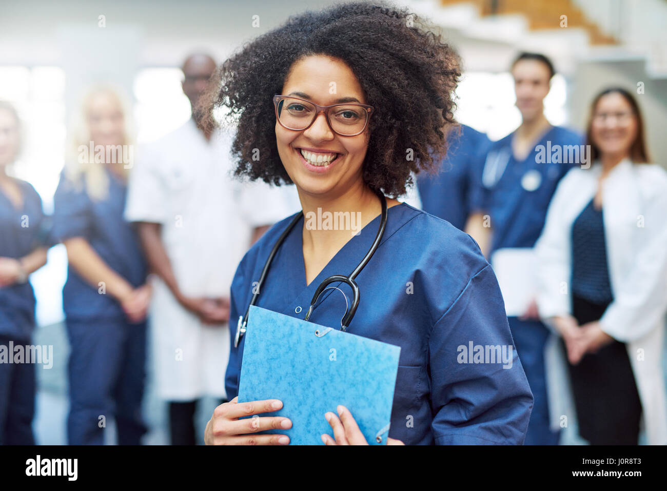 Smiling young black female doctor standing in front of medical team at hospital Stock Photo