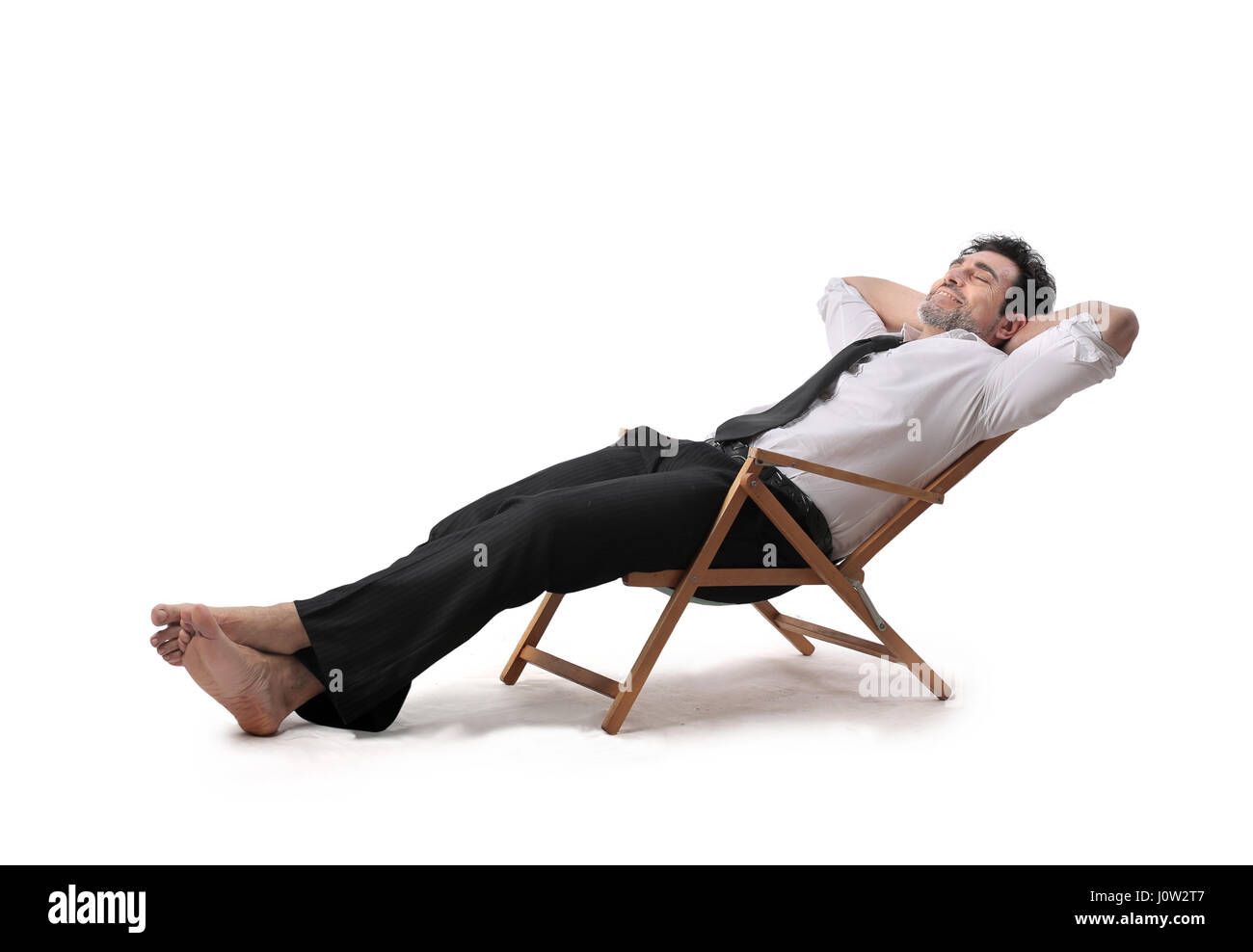 Businessman relaxing on beach chair - Stock Image