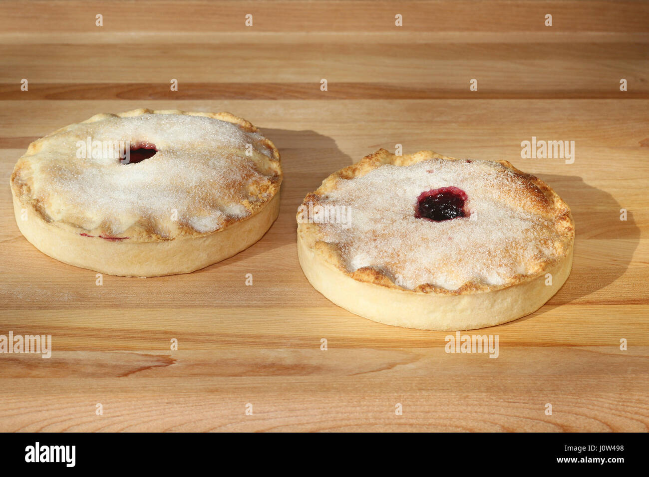 Cherry pie and and blueberry pie sprinkled with sugar on pastry board - Stock Image