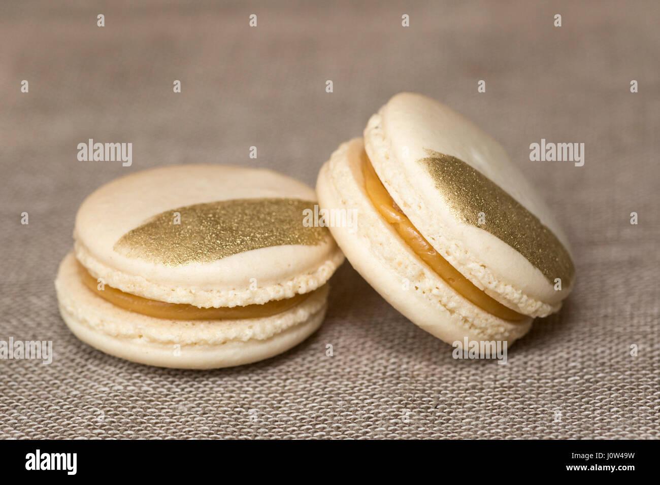 Salted caramel macarons on Irish linen - Stock Image